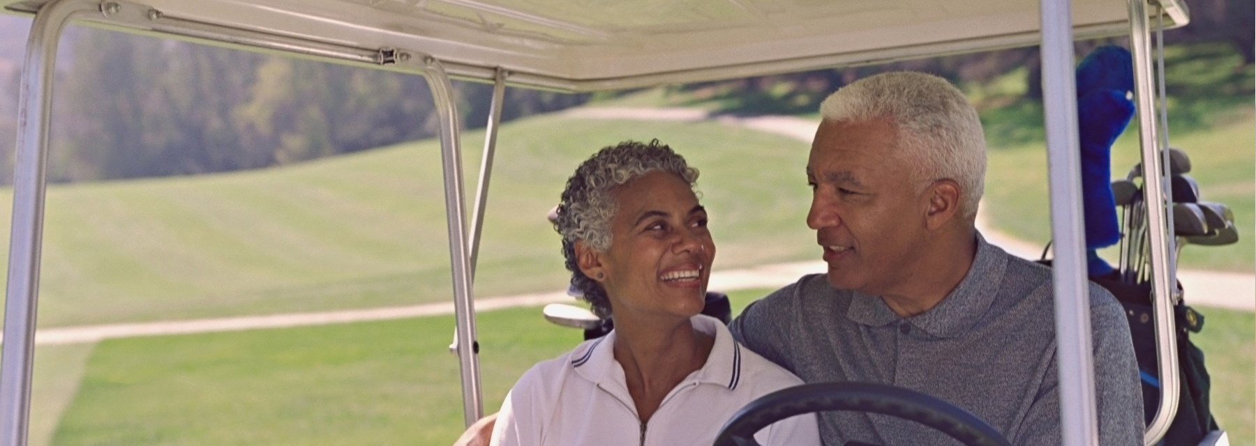 elderly couple sitting in golf cart